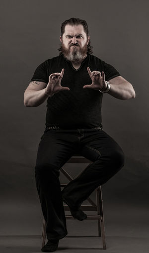 Angry Mid Adult Man Gesturing While Sitting Against Black Background