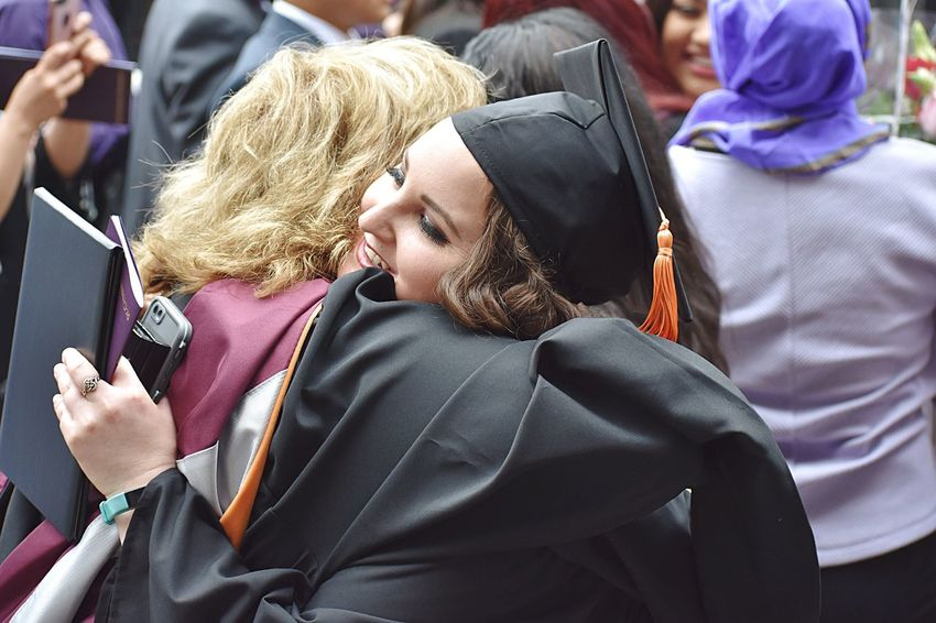 Professor hugging student at graduation Robe Adult College University Graduation Celebration Hug Professor Student Real People Clothing Lifestyles People Women Wireless Technology Adult Smart Phone Incidental People Traditional Clothing Communication Mobile Phone Group Of People Portrait Connection Day Technology Outdoors