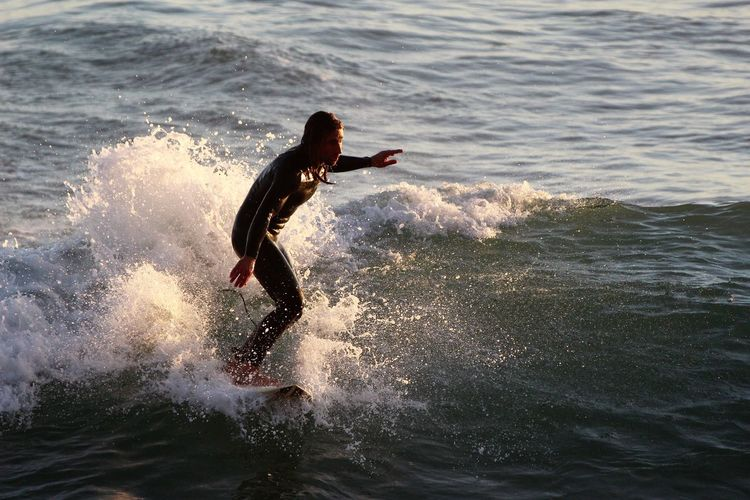Woman surfing in sea during sunset