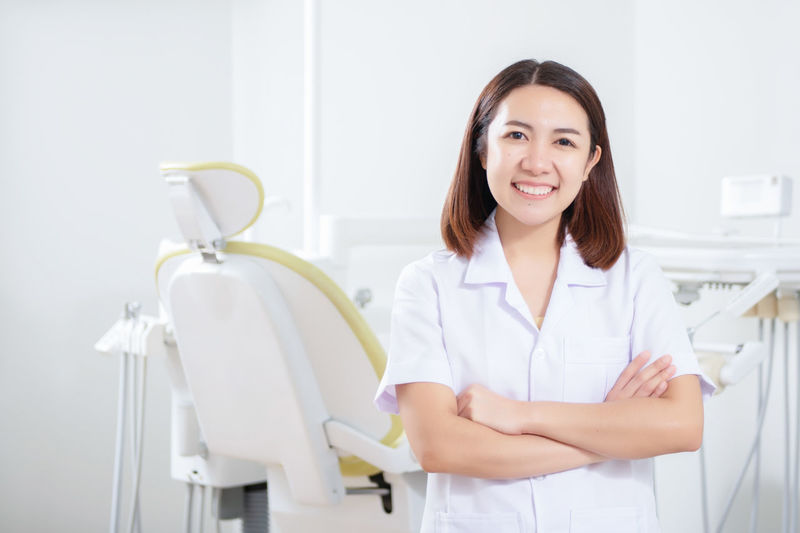 Portrait of female dentist Looking At Camera Smiling Portrait Front View One Person Indoors  Waist Up Occupation Women Healthcare And Medicine Happiness Doctor  Adult Female Doctor Lab Coat Confidence  Hairstyle Dental Dentist Clinic Hospital Office Dental Health