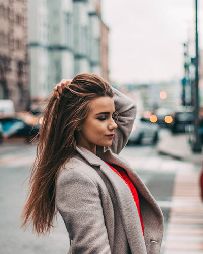 Beautiful woman standing on street in city