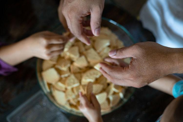Kids making kek batik or malaysian triple chocolate dessert. crushing the cookies into tiny pieces.