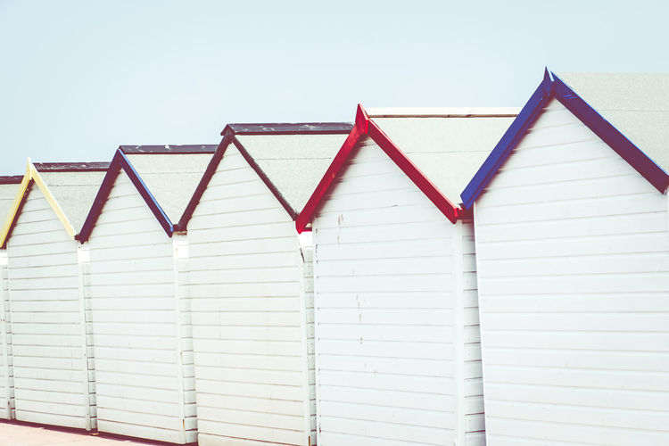 Row Of Colourful Seafront Beach Huts Colourful Devon UK Paignton Beach Preston Green Roof Wooden Huts Wooden Hut Architecture Beach Huts Building Exterior Clear Sky Close-up Colorful Day Hut Huts No People Outdoors Paignton Roofs Seafront Seaside Sky Summer White Background