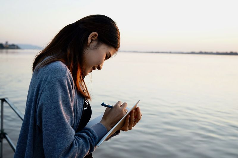 Side view of young woman writing in book by lake against clear sky