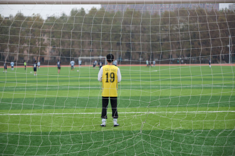 Rear view of man playing soccer on field