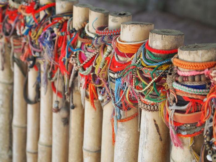 Close-up of multi colored objects tied on bamboos