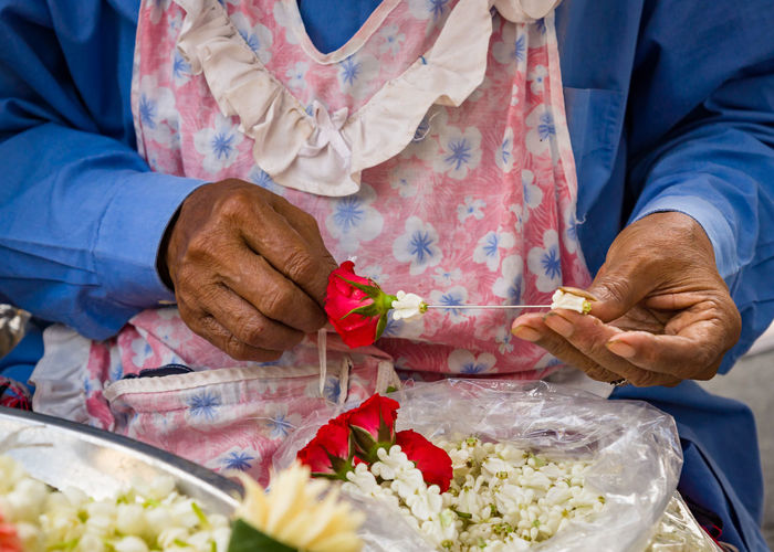 Midsection of woman making garland
