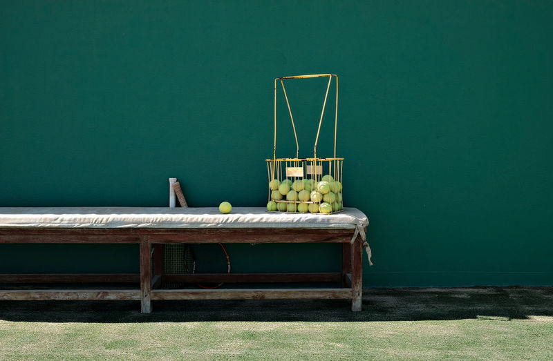 Tennis balls in metallic basket on bench against wall