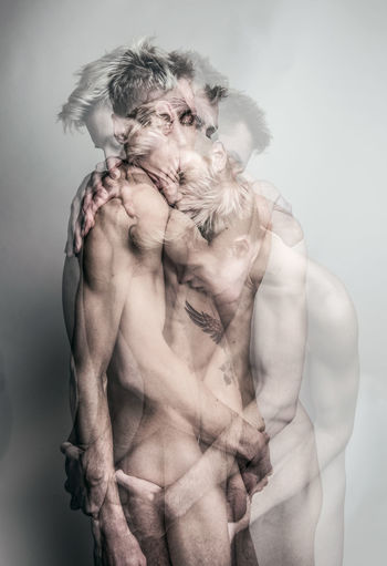 Digital Composite Image Of Shirtless Gay Men Embracing Against Gray Background