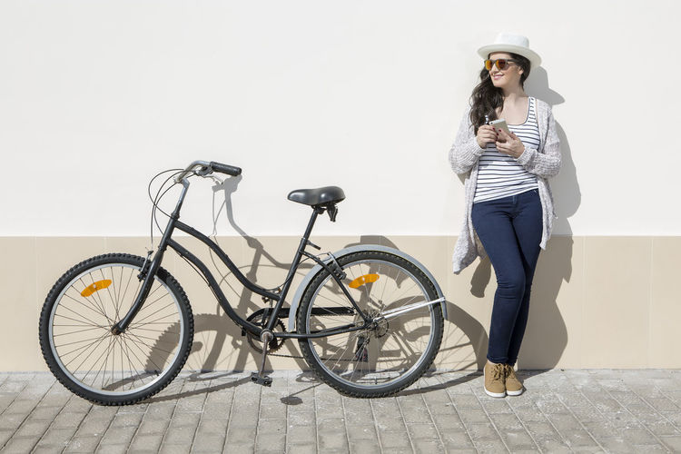 Young female tourist with smartphone standing nearby bike against wall in Lanzarote, Spain. Person, Woman, Smartphone, Vacation, Gran Canaria, Technology, Bicycle, Spain, Travel, Lifestyle, Smile Device, Holding, Gadget, Connection, Standing, Bike, Tourism, People, Young, Adult, Female, Summer, Lanzarote, Transport, Leisure, Tourist, Beautiful,