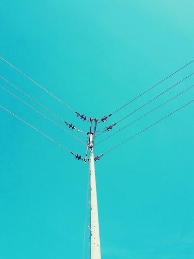 Low angle view of electricity pylon against clear blue sky during sunny day