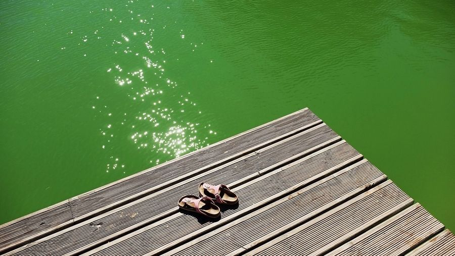High Angle View Of Sandals On Pier Over Lake