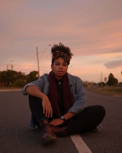 Young Woman Sitting On Road Against Sky During Sunset