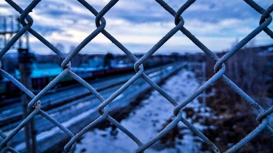 Close-up of chainlink fence against sky during winter