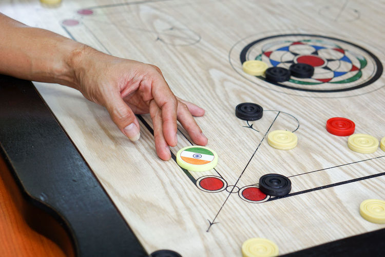 Human Hand Human Body Part High Angle View One Person Indoors  People Adult Adults Only Skill  Game Playing Play Carrom Carromboard Carom India Striker Red Black White Tournament