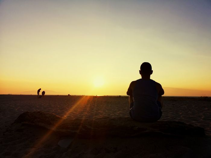 Rear view of silhouette young man sitting on beach against sky during sunset