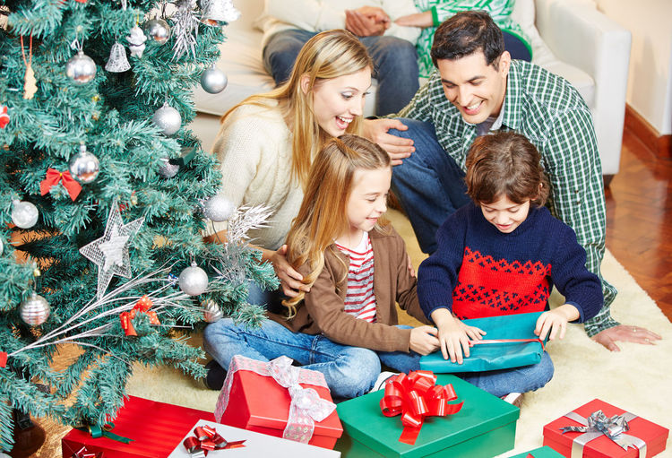 Cheerful brother and sister sitting with parents opening gifts at home during christmas