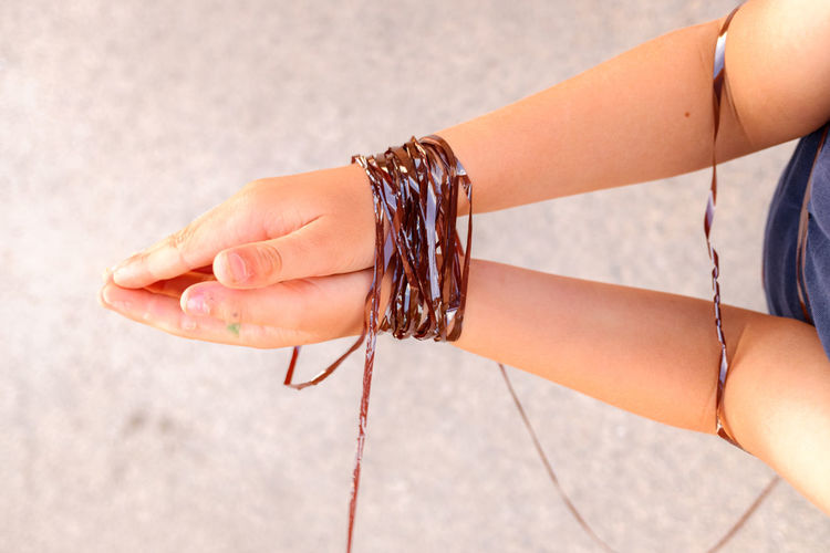 Cropped hands of person tied with reel over land