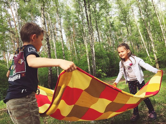 Siblings Holding Picnic Blanket On Field Against Trees In Forest