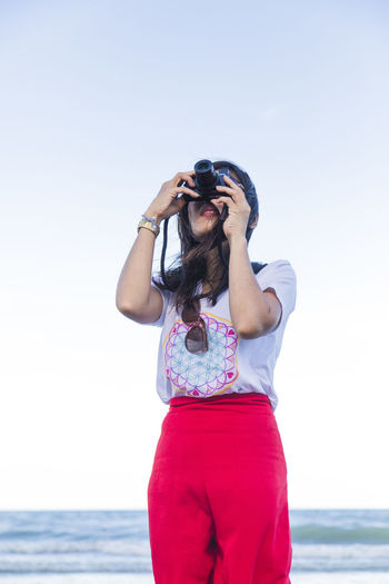 Midsection of woman photographing against sky