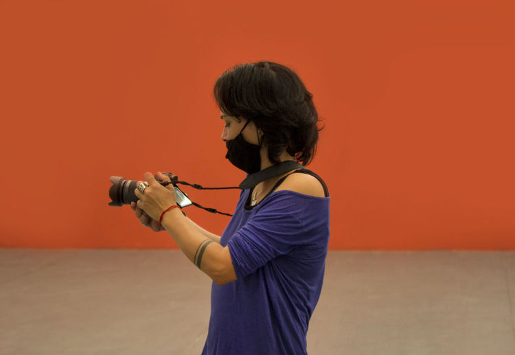 Side view of senior woman standing against orange wall