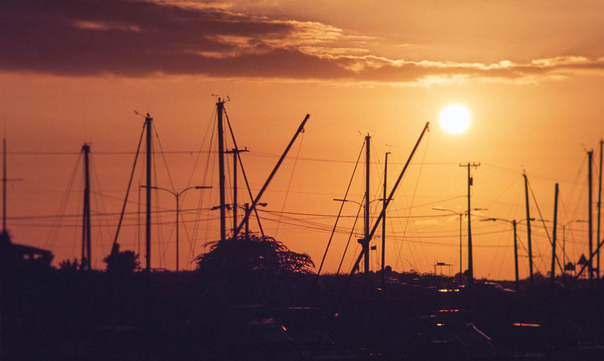 Silhouette sailboats against sky during sunset