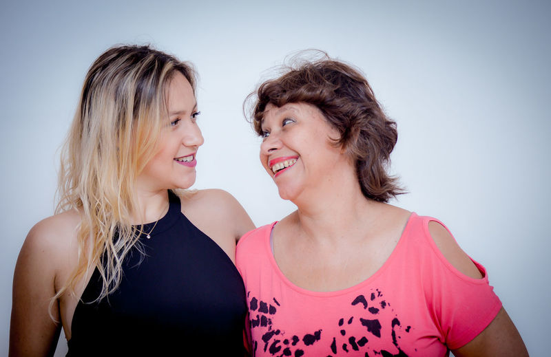 Close-up of happy women against white background