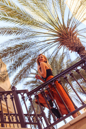 Beautiful woman standing against palm tree