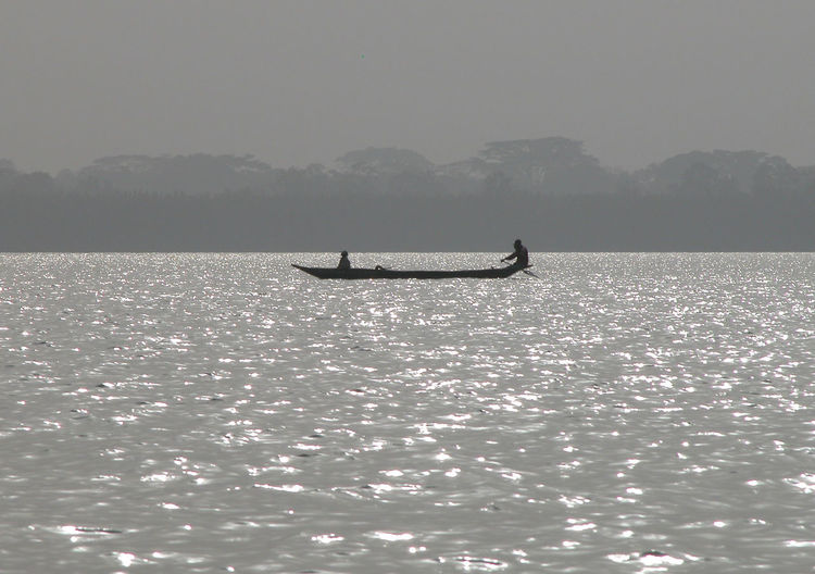 Distant view of men sailing boat on sea