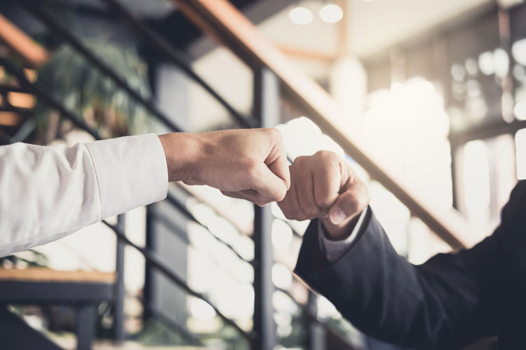 Cropped image of businessmen fist bumping in office