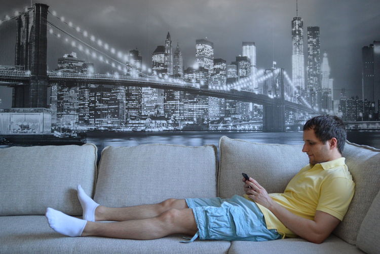 Side view of man reclining on sofa while using mobile phone against picture frame at home