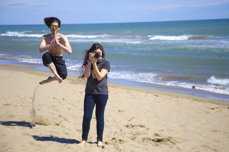 Shirtless Man Jumping At Beach While Female Friend Photographing