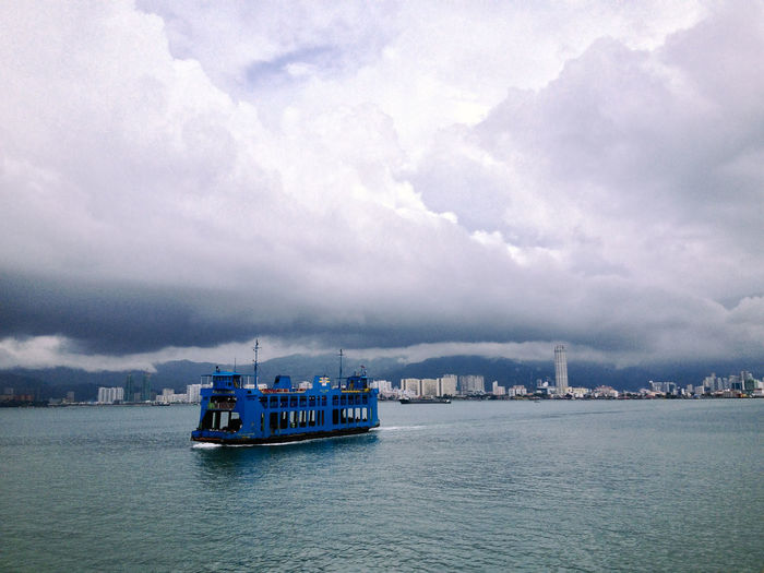 Ferry sailing on lake against cloudy sky