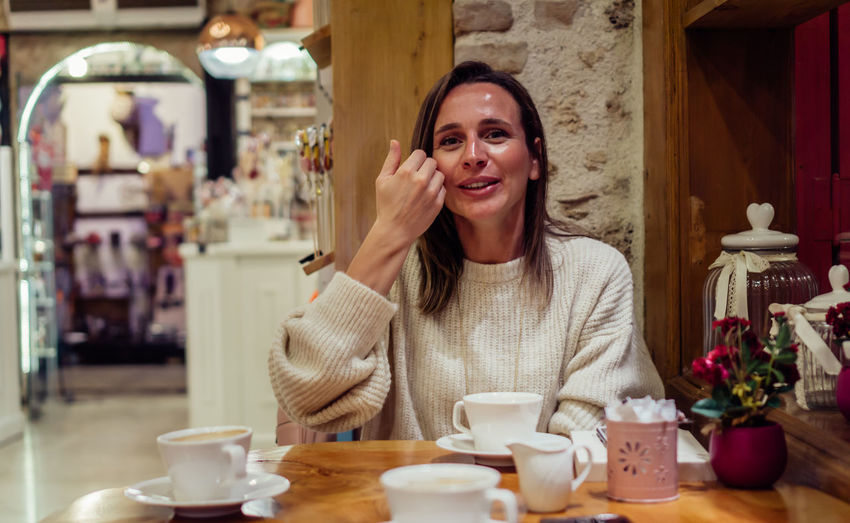 Portrait of smiling woman with coffee at cafe