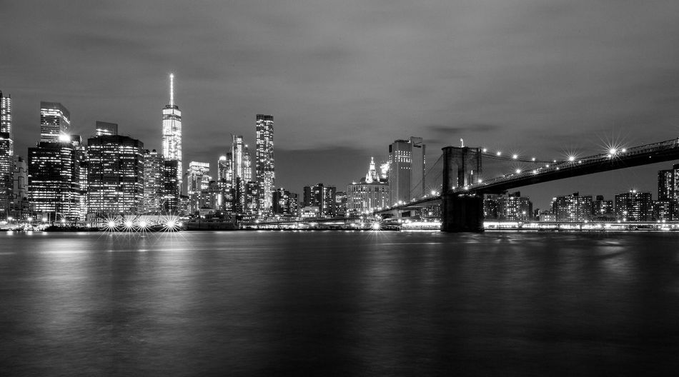 Brooklyn Bridge Over East River By Illuminated City Skyline Against Sky At Dusk