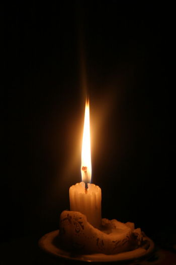 Close-up of burning candle in darkroom