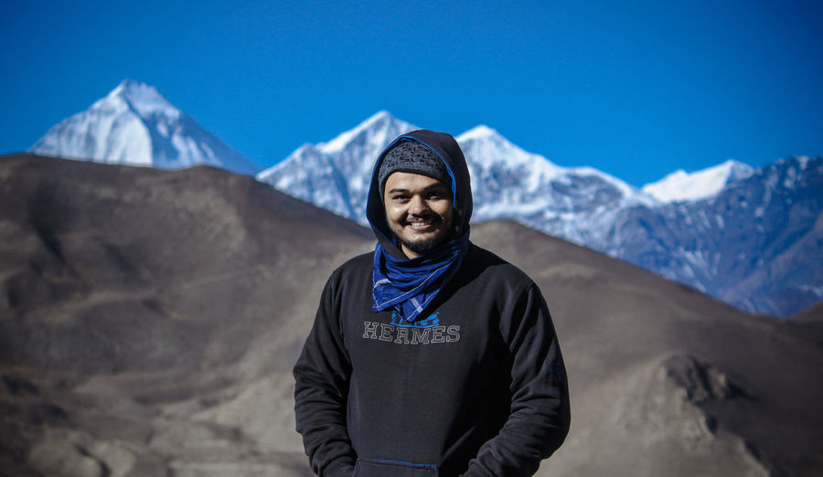 Portrait of young man standing on snowcapped mountain against sky