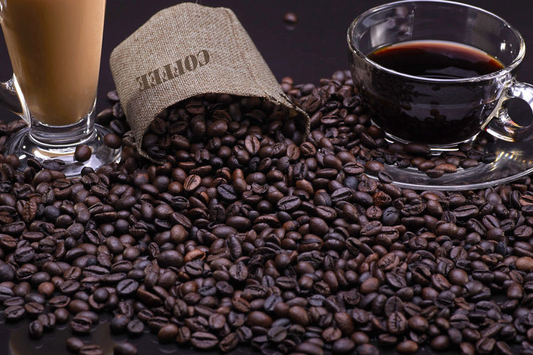 A cup of coffee with coffee beans over the black background Drink Food And Drink Refreshment Coffee - Drink Coffee Roasted Coffee Bean Freshness Brown Food Indoors  Coffee Bean Still Life Glass Large Group Of Objects No People Abundance Cup Caffeine Close-up Mug Crockery