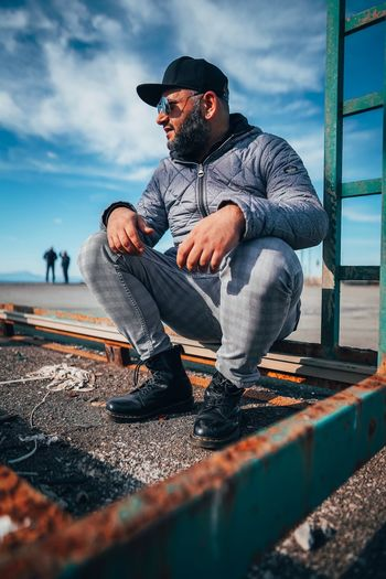 Man sitting on old rusty metal against sky
