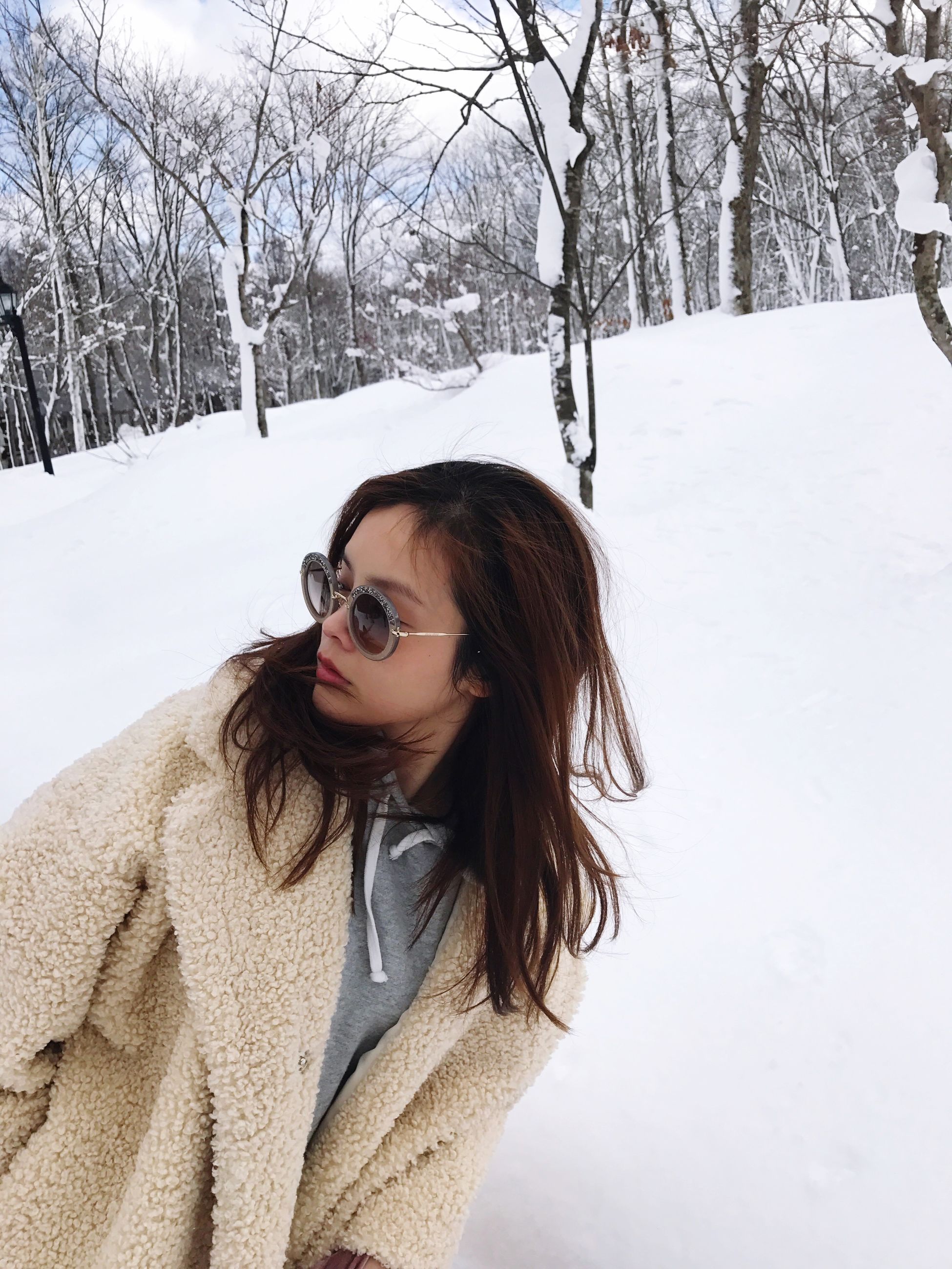 winter, young adult, cold temperature, sunglasses, looking at camera, portrait, snow, lifestyles, young women, one person, leisure activity, nature, warm clothing, one young woman only, one woman only, tree, outdoors, women, people, adult, vacations, day, real people, adults only, beautiful woman, only women, human body part