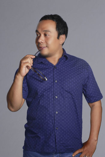 Portrait young asian man standing with glasses in his hand Only Men One Man Only Studio Shot One Person Gray Background People Adults Only One Young Man Only Standing Smiling Indoors  Happiness Portrait