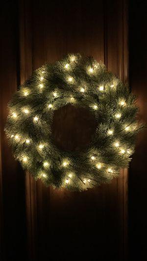 Illuminated christmas tree against wall