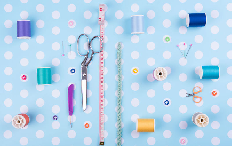Directly above shot of sewing item arranged on blue polka dot background