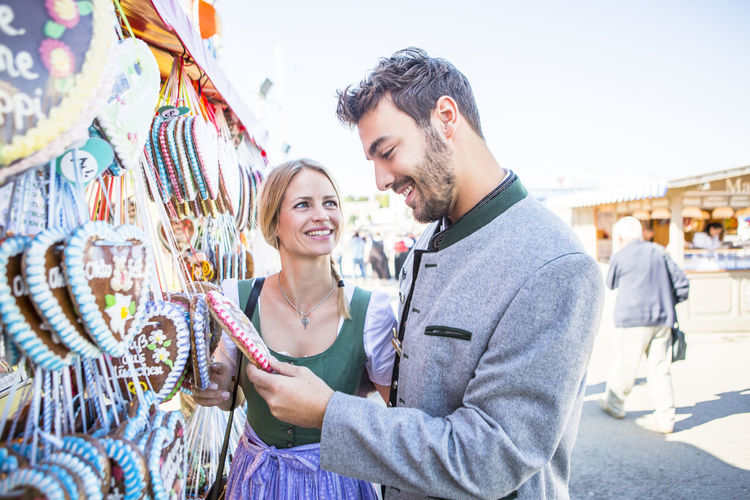 A young German choosing which ginger bread heart to buy at a stall at the Octoberfest festival held at the Theresienwiese in Munich, Germany Bavarian Girl Bavarian Man Bavarian Style Couple Dirndl Enjoyment Festival Flirt Freedom German Style Germany In Love Lederhosen Munich München Octoberfest Party Relationship Style Theresienwiese Tracht Wiesn Young Young Couple Youth