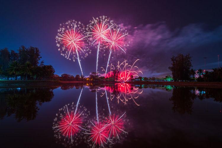 Firework display over lake against sky