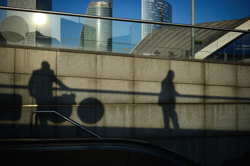 Shadow of man walking on glass building