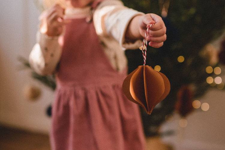 Midsection of girl holding home made christmas ornament indoors