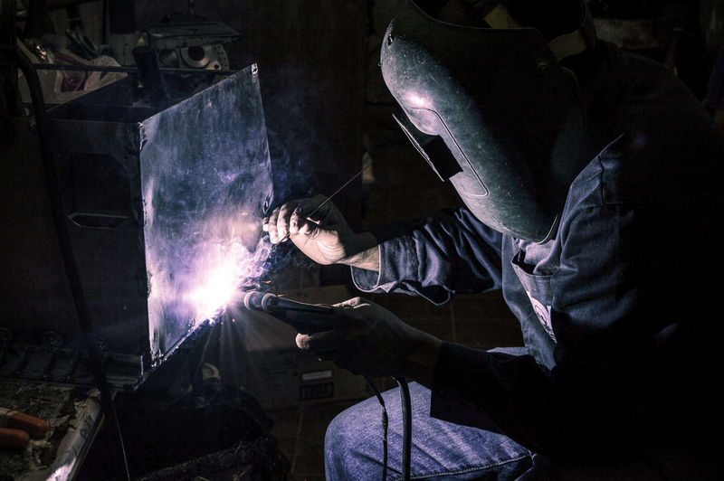 Man working on metal in container