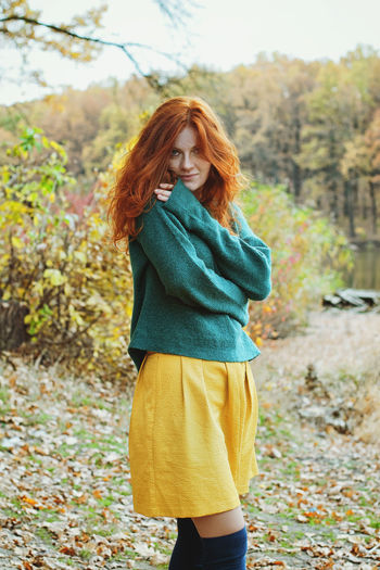 Young redhead woman in green sweater stay near lake in autumn park.