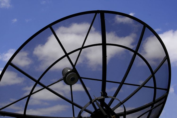 A television satellite receiver dish in use Architecture Close-up Cloud - Sky Communication Connection Day Low Angle View Metal No People Outdoors Reception Satellite Dish Satellitedish Sky Technology Television Receiver